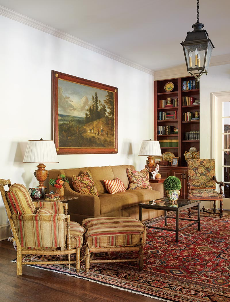 The dens warm atmosphere comes from a muted mix of fabrics an antique oriental rug and a large landscape painting that blends beautifully with the color
