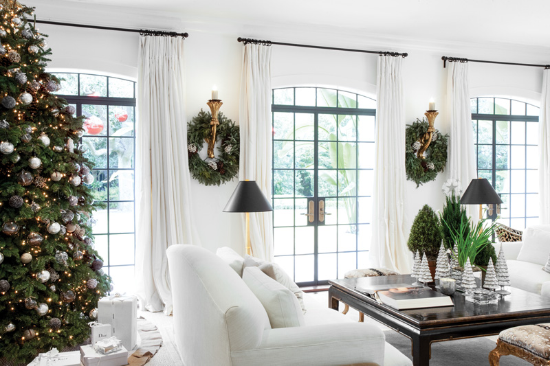 Elegant Christmas decor in a white family room with wreaths around gold sconces