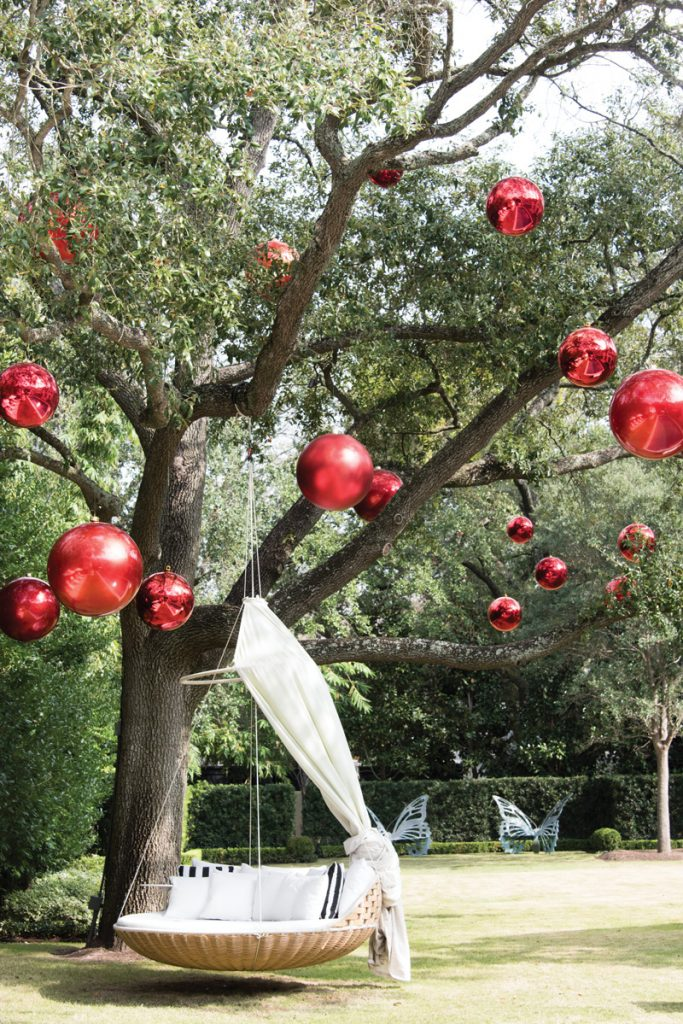 Giant red ball ornaments hung from a tree for Christmas outdoor decor