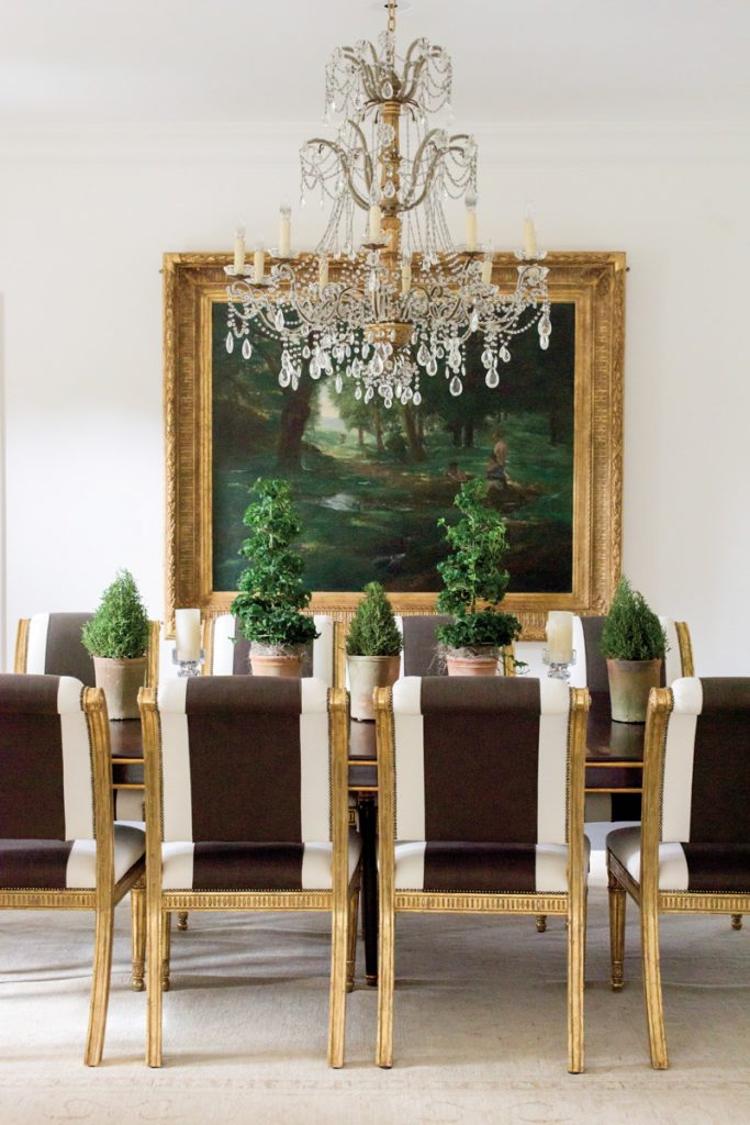 Elegant dining room with crystal chandelier, wide stripe on chairs, and gold gilding on furniture and art frame