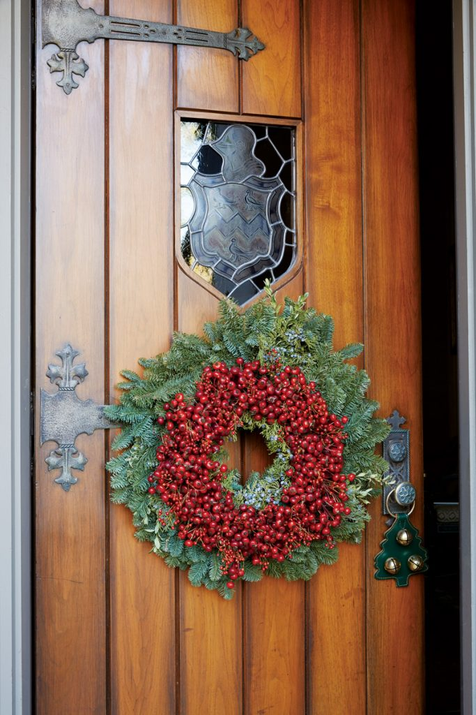 Exquisite vintage planked door decorated with a Christmas wreath with red berries