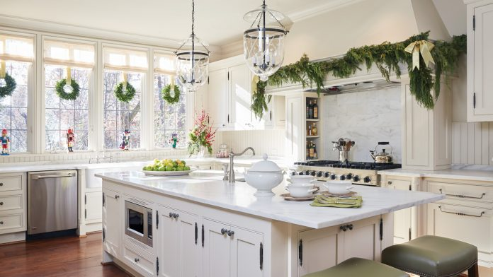 Beautiful white kitchen with beadboard decorated for Christmas with fresh greenery