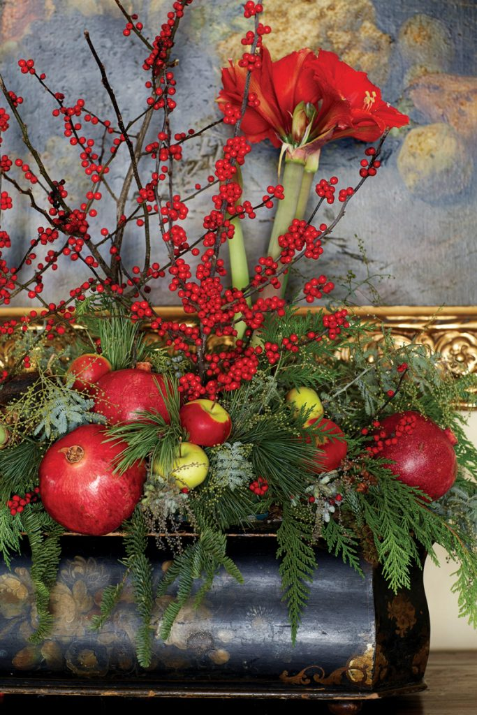 Vivid red apples, pomegranates, berries and flowers in a Christmas floral arrangement