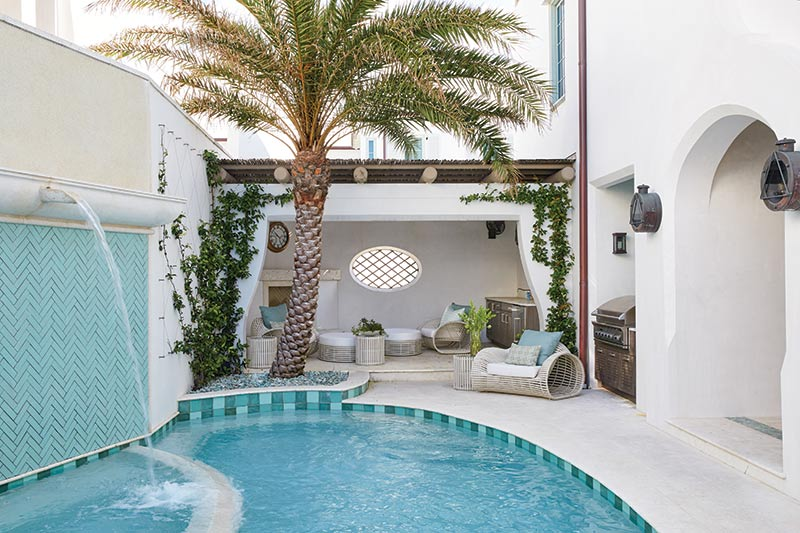 Pool with palm tree and lounge chairs.