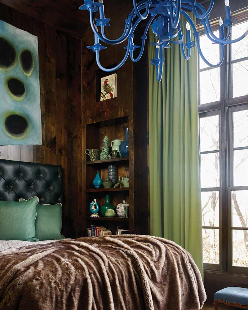 royal blue chandelier, fur throw, and wood-paneling in master bedroom