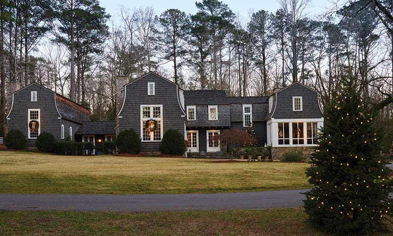dark gray shingled home with Christmas wreaths