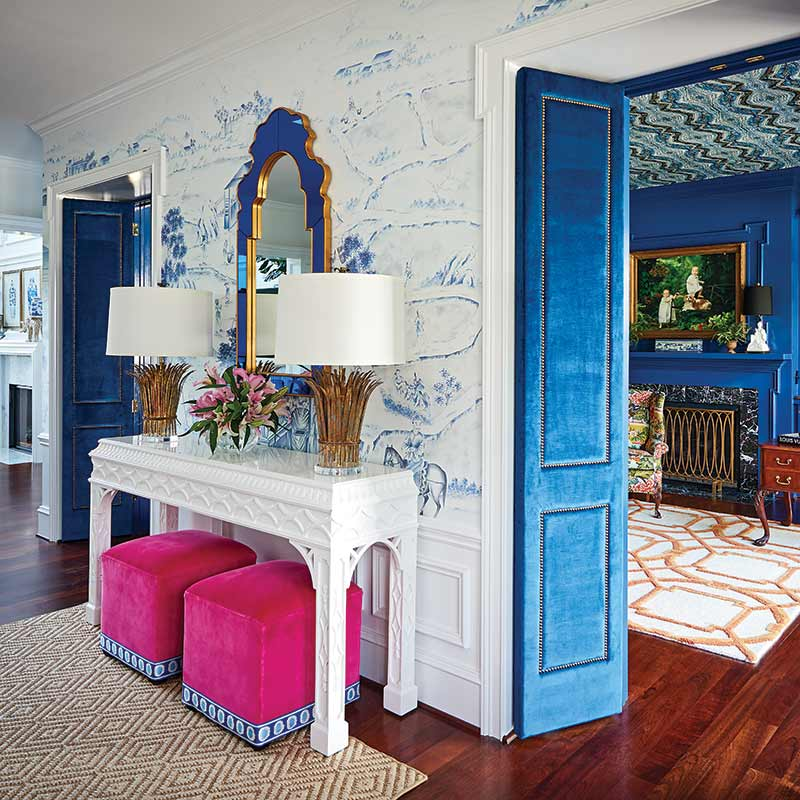 front entry with blue-and-white wallpaper and pink upholstered cubes